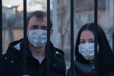 EinMann und eine Frau mit Masken stehen hinter einem Zaun